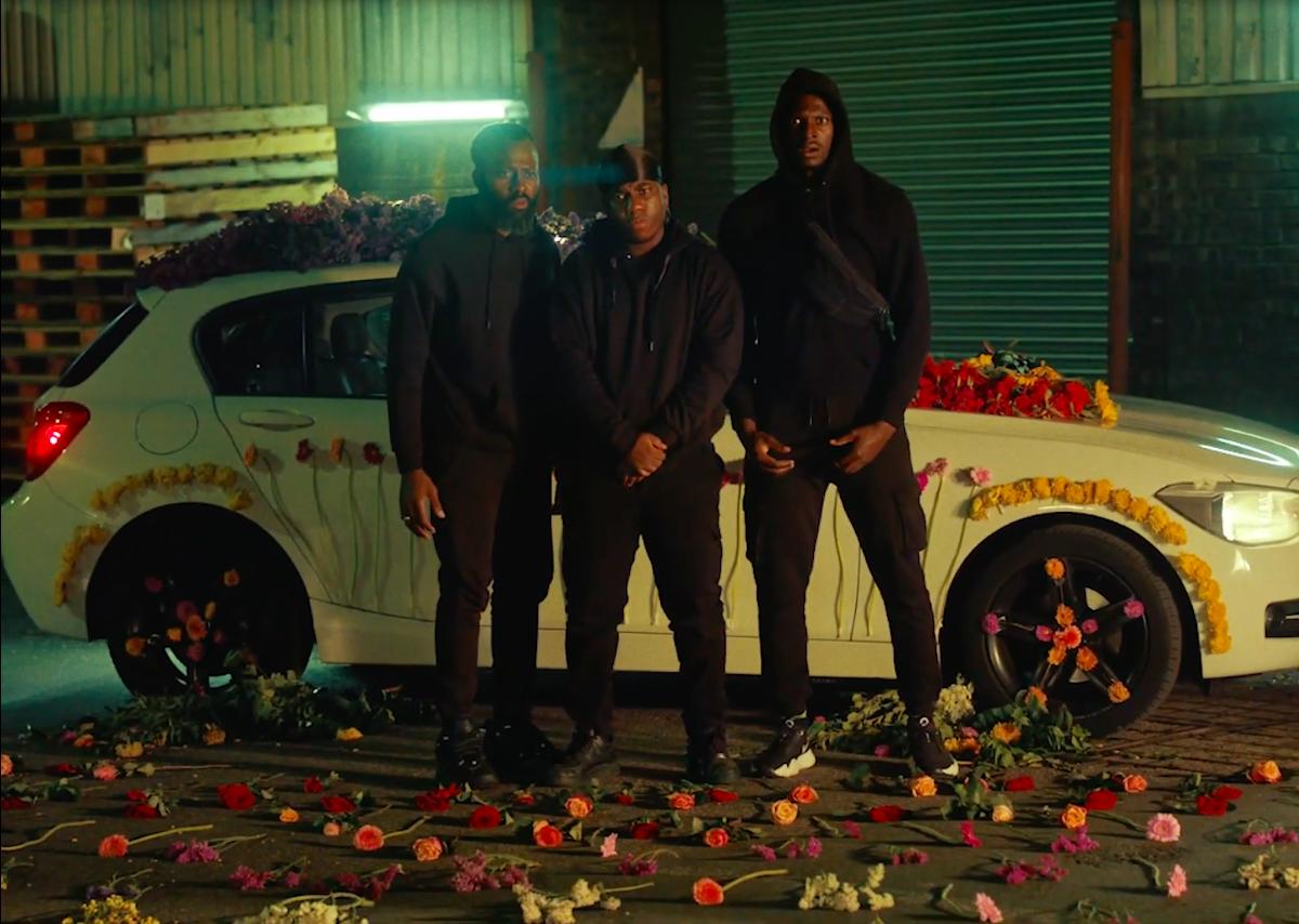 Trois hommes en noir devant une voiture avec des fleurs au sol Image du clip Flowers du chanteur américain AaronTaylor sur le média de musique émergente KAO Magazine